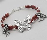 Bijuterii noi: Bratara in stil tribal din sfoara portocalie cerata impletita cu pandantive din argint: flori, frunze si fluture